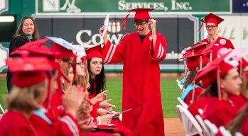 A Northwestern Regional High School graduate celebrates has he makes his way back to his seat after receiving his diploma during graduation ceremonies Wednesday at Dunkin' Donuts Park in Hartford. Jim Shannon Republican American