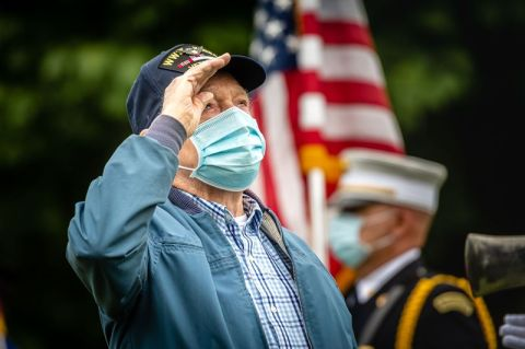 Mark Baker, 94, a Navy veteran of World War II and the Korean War, stands at attention saluting the U.S. flag during the playing of the national anthem at Memorial Day ceremonies on the green in Prospect on May 25 of last year. Baker died two months later. (Bill Shettle Republican-American)