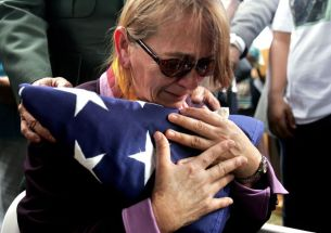 Norma Mendez, the mother of U.S. Army soldier Antonio Mendez, who was killed in Iraq in late 2005, embraces an American flag that was ceremoniously folded and presented to her at her son's burial in Rincon, Puerto Rico, on Dec. 2, 2005. Antonio Mendez was killed in Kirkuk, Iraq, on Nov. 11, according to Army authorities. He was 22. (AP Photo/Brennan Linsley)