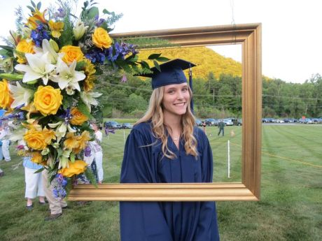 Gavrayla Schuster poses in a frame designed by the floral arrangement class during Housatonic Valley Regional High School's graduation Thursday in Falls Village. A total of 67 seniors graduated. Ruth Epstein Republican-American