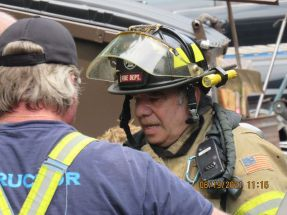 Mel Brenner, the newest member of the Woodbury Volunteer Fire Department, confers with an instructor prior to entering the mockup of a fire-ravaged bedroom to search for trapped victims in the June 19 drill.Contributed/WVFD