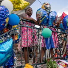 Melodi Butler, 6, stands on a stoop beside a makeshift memorial at the scene where 10-year old Justin Wallace was shot and killed the previous Saturday night in the Rockaway section of the Queens borough of New York, on Wednesday, June 9, 2021. Police arrested Jovan Young, 29, on Tuesday in connection with the death, with charges including murder, attempted murder and assault. (AP Photo/John Minchillo)