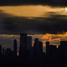 The sun is partially eclipsed by the moon as it rises over lower Manhattan in New York, Thursday, June 10, 2021. (AP Photo/Seth Wenig)