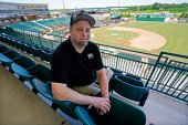 """Baseball fan Josh Smith sits in a seat in The Ballpark at Jackson on Tuesday, June 22, 2021, in Jackson, Tenn. When Major League Baseball stripped 40 teams of their affiliation in a drastic shakeup of the minor leagues this winter, Jackson lost the Jackson Generals, the Double-A affiliate of the Arizona Diamondbacks. Smith said he misses going to Generals games with family members and friends. """"It was what baseball was always supposed to be,"""" he said. """"It's your whole community having a blast."""" (AP Photo/Mark Humphrey)"""