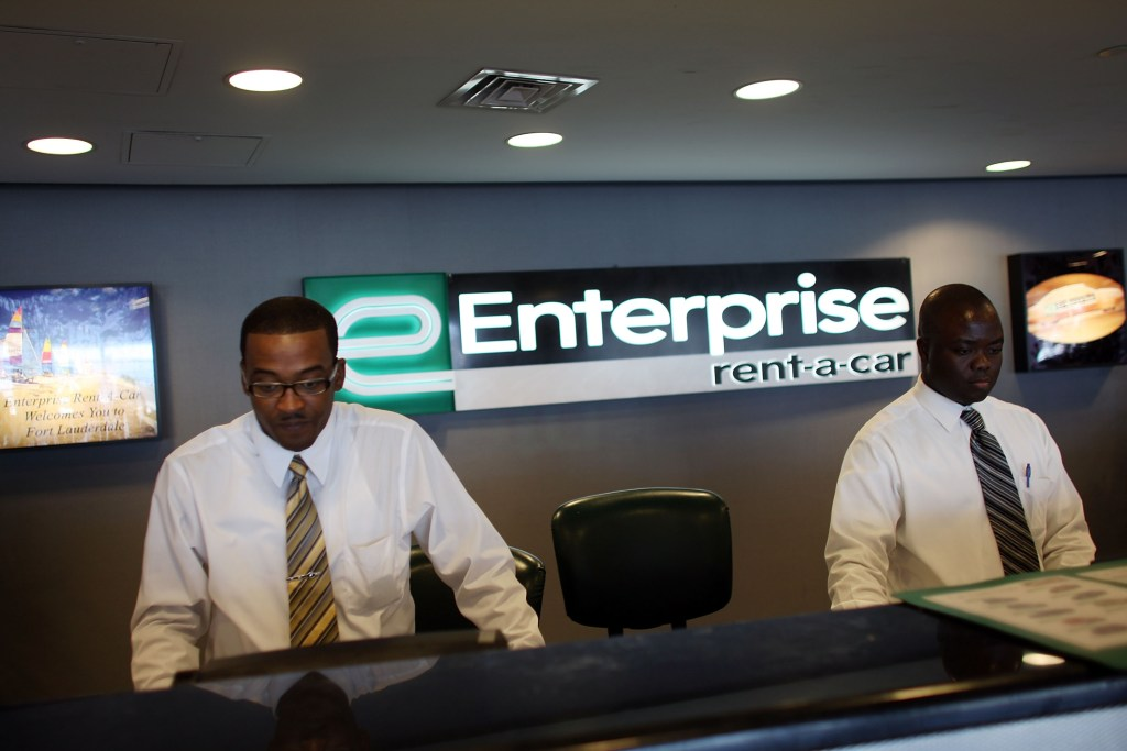 Customer service representatives Oneal West, left, and Marmontel Michel wait on customers at Enterprise Rent-A-Car at the Fort Lauderdale/Hollywood International airport July 10, 2007, in Fort Lauderdale, Fla. ( Joe Raedle/Getty Images News file)