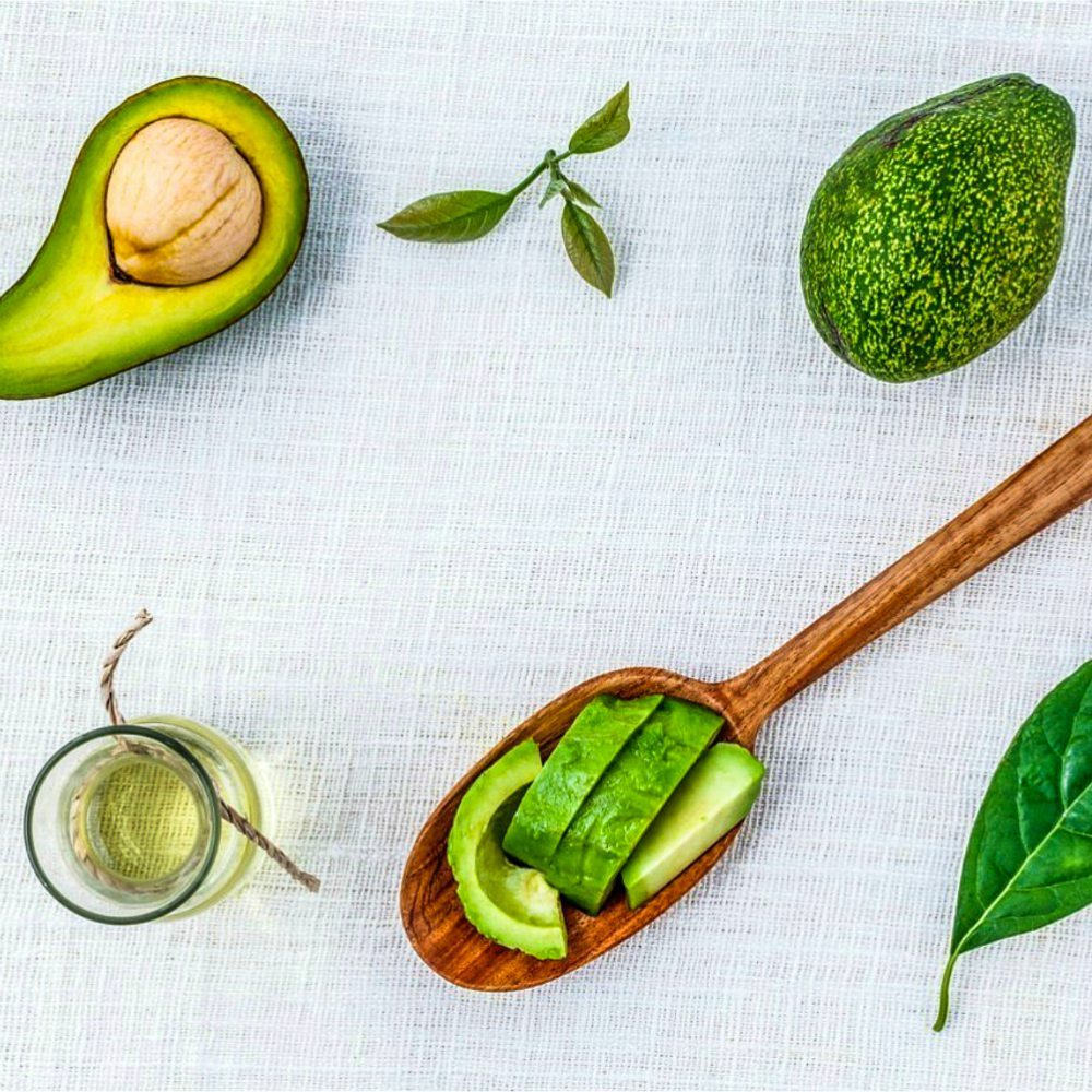 An image of avocados, avocado oil, and leaves