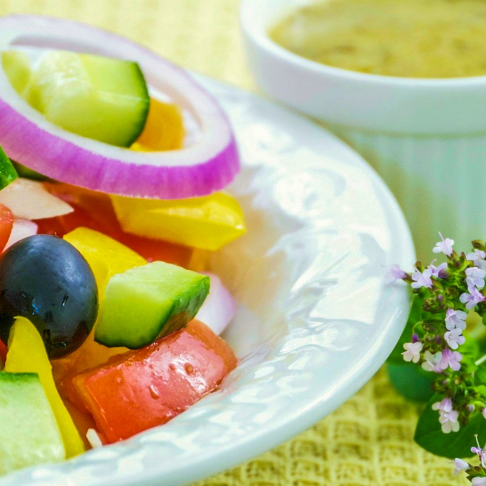 An image of a bowl of vegan greek salad with a small bowl of salad dressing next to it