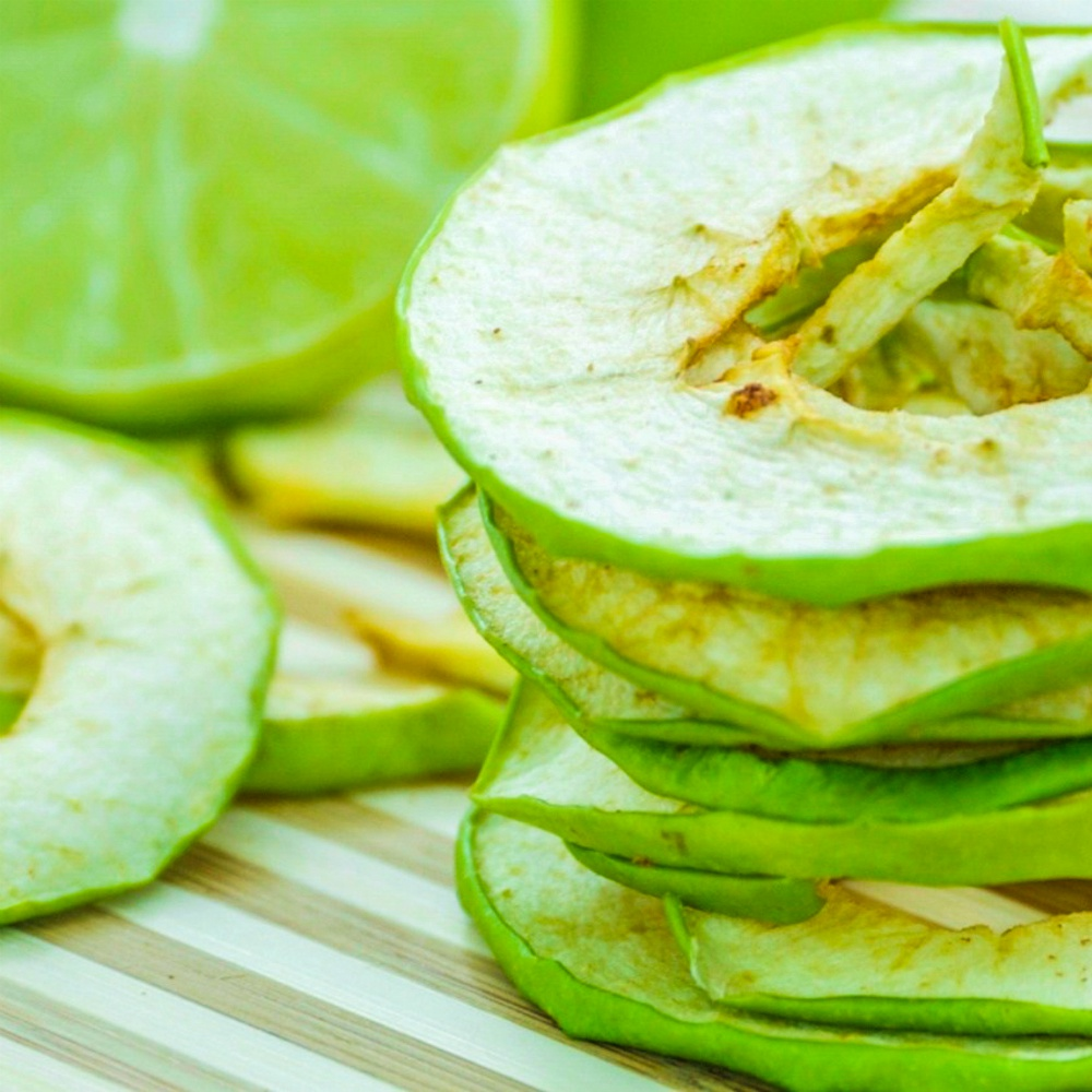 An image of sour apple chips and a sliced lime