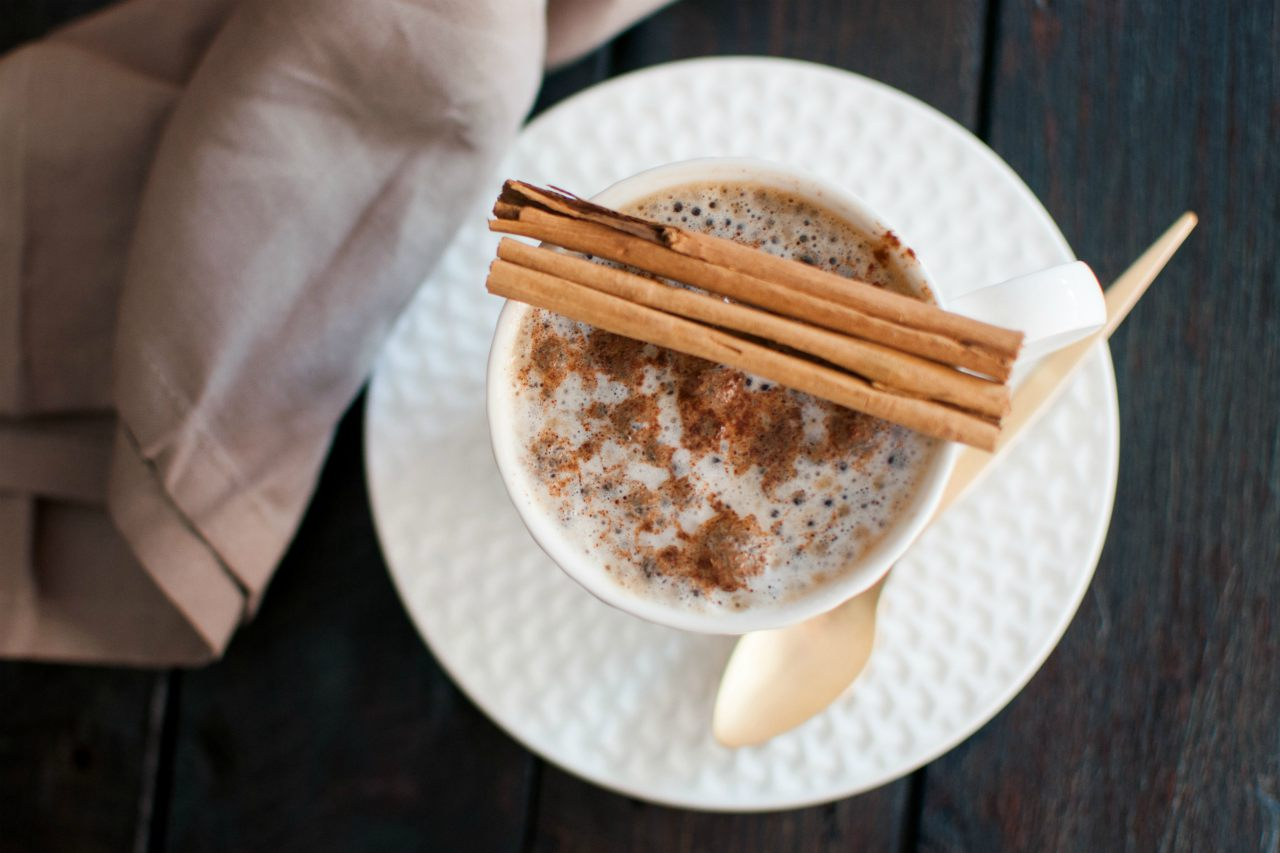 An image of a cup of tea topped with ground cinnamon, with cinnamon sticks balanced on top of the tea cup
