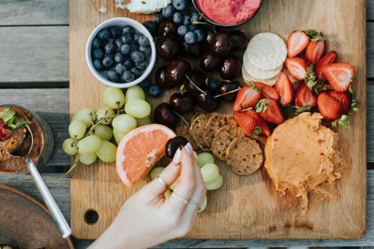 An image of a womans hand taking a piece of fruit off of a healthy snack platter