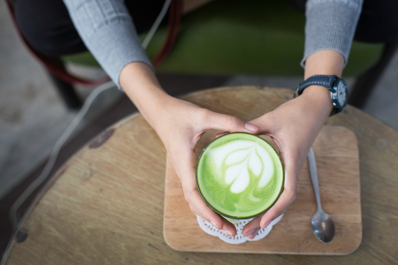 An image of a womans hands holding a mug containing matcha