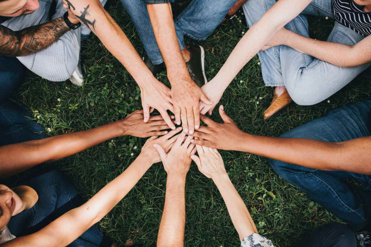 An image of a group of people all putting their hands in a circle