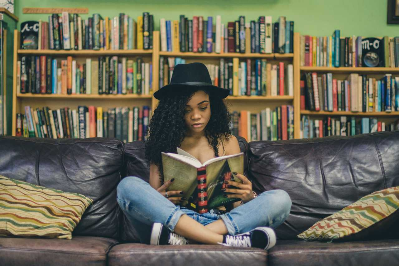 An image of a woman sitting on a couch reading a book