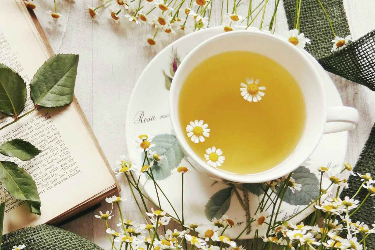 An image of a tea cup containing chamomile tea next to chamomile flowers and a book