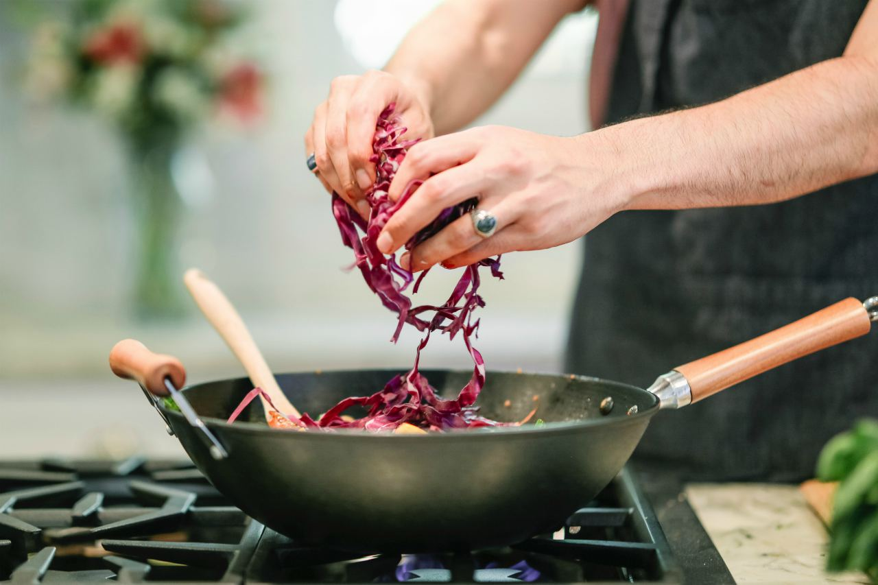 An image of a man adding chopped red cabbage to a frying pan