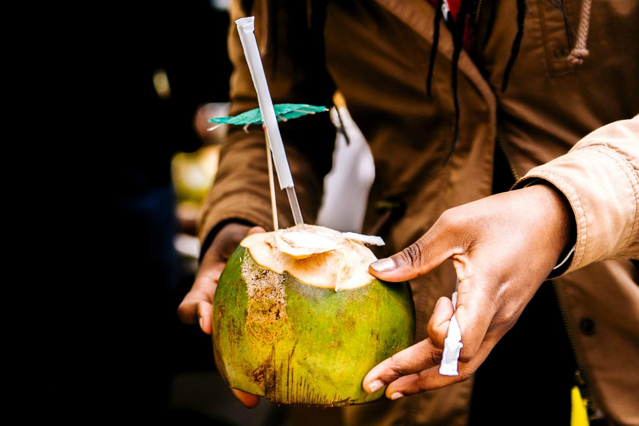 An image of a persons hands holding a fresh coconut with the top chopped off with a straw in it