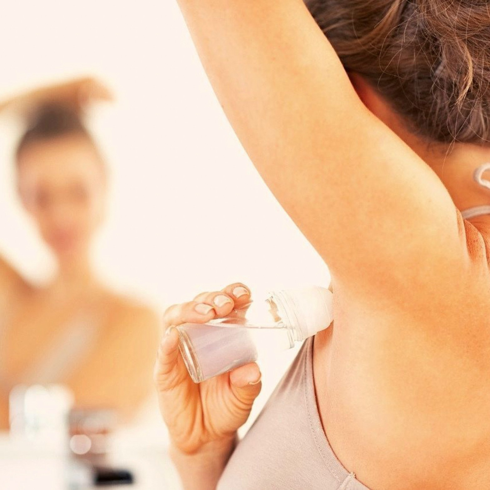 An image of a woman putting on deodorant