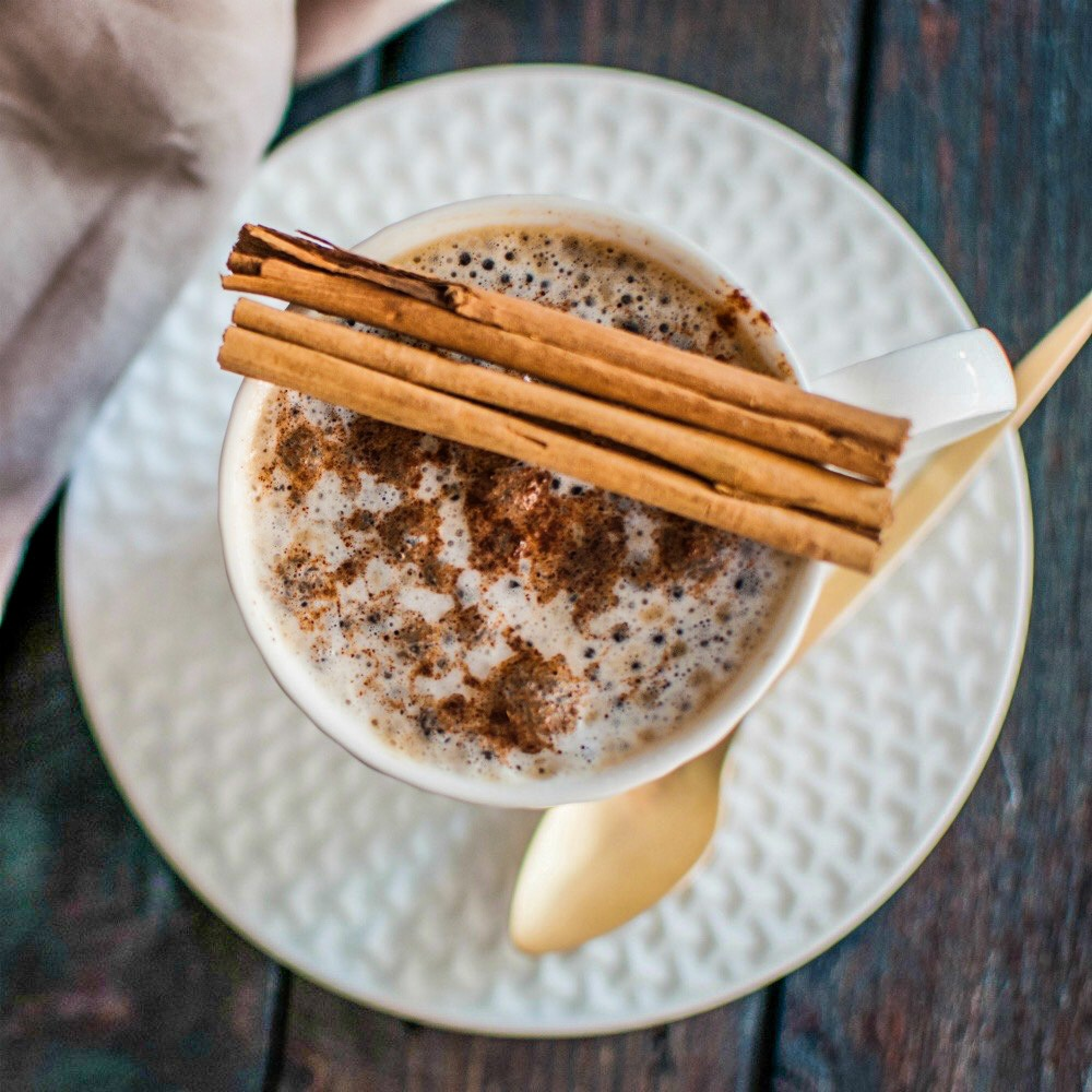 An image of a cup of tea topped with ground cinnamon and cinnamon sticks.