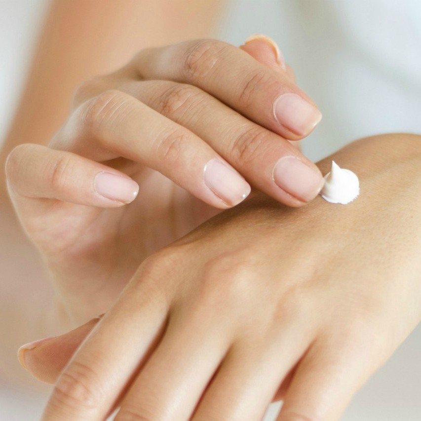 An image of a woman putting moisturizer onto the back of her hand.