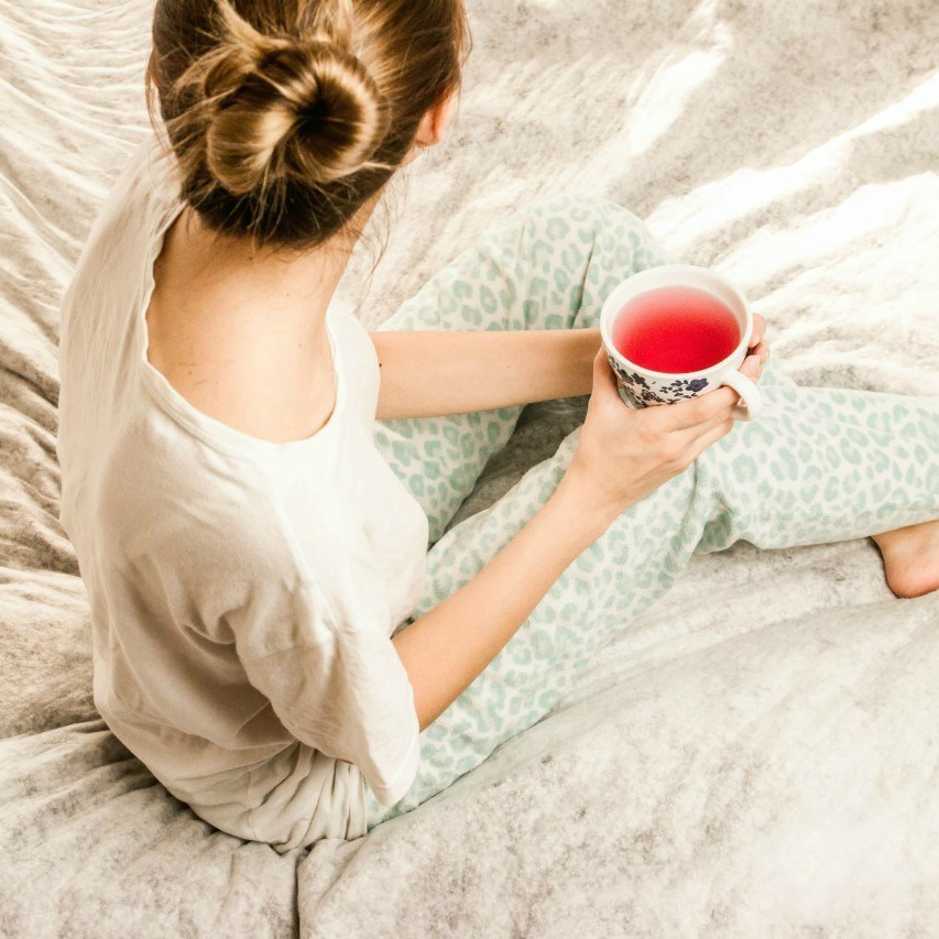 An image of a woman in pyjamas sitting on a bed holding a cup of tea.