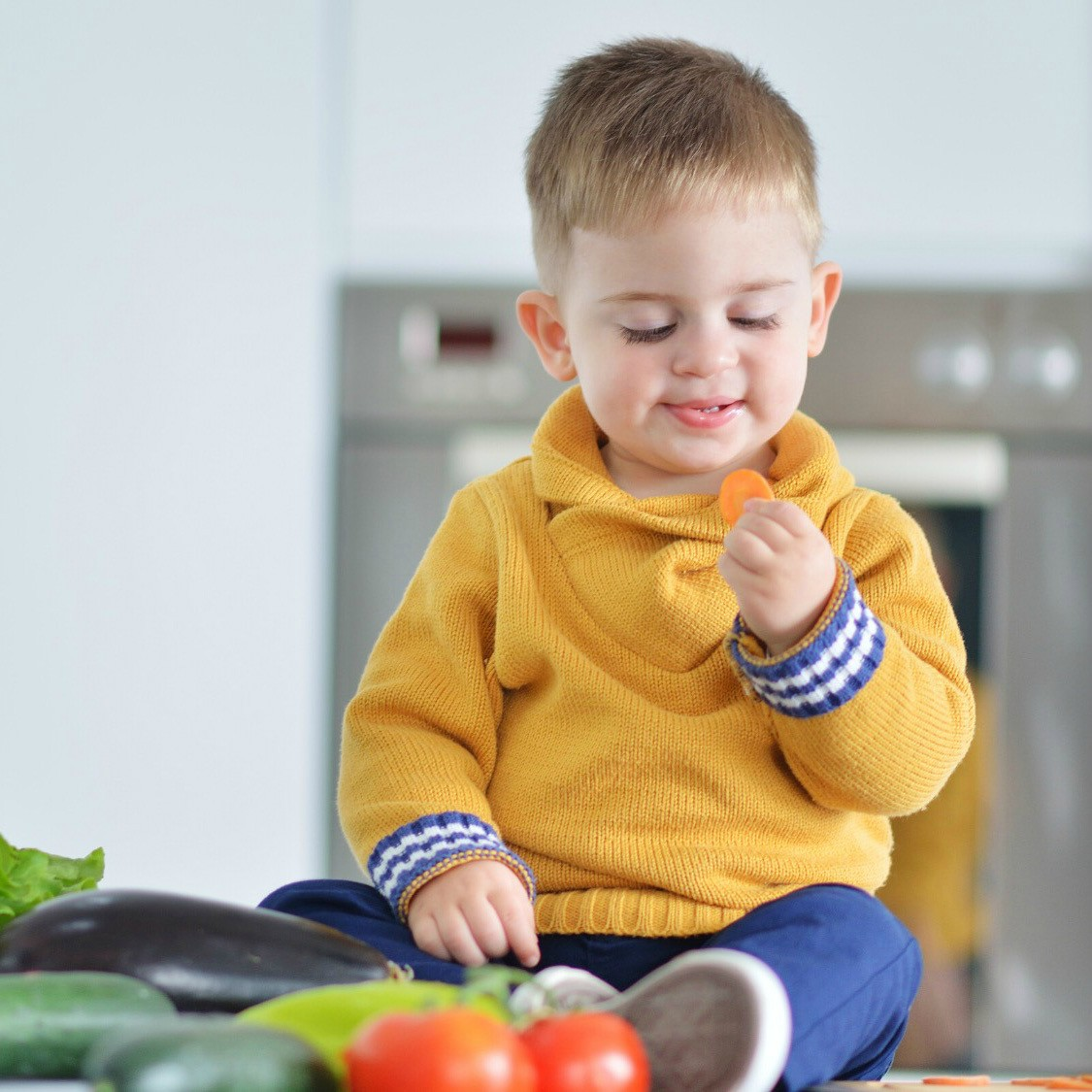 An image of a toddler eating carrots.