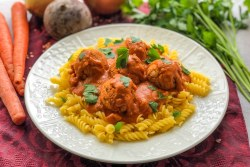 An image of a plate of vegan veggie meatballs on pasta.