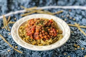 An image of edamame fettuccini topped with instant pot lentil bolognese.
