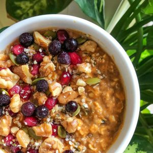 An image of bowl of pumpkin pie overnight oats topped with pomegranate seeds, frozen blueberries, chopped walnuts, hemp seeds, and pumpkin seeds.