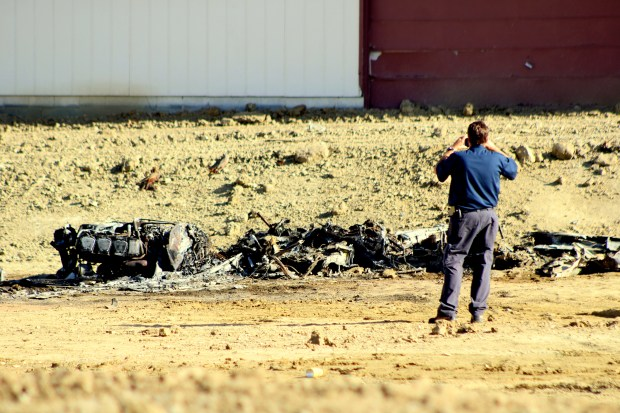 An investigator takes photos of the plane wreck off County Road on Wednesday. (Hans Peter / Reporter-Herald)