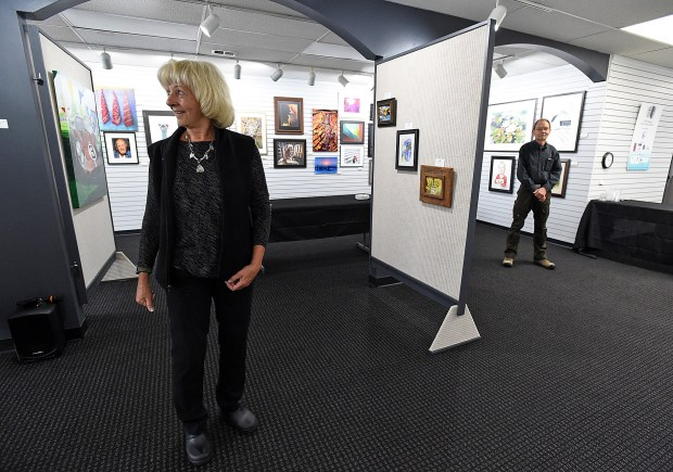 Bonnie Stahlin, president of the Board of Directors for the Lincoln Gallery, talks about partitions were added to create more space for artwork for the gallery's 2019 National Fine Art Show. (Jenny Sparks/Staff Photographer)