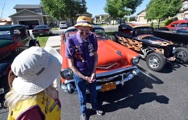 Art Kimble chats with fellow Loveland Lions Club member Deb Stucklen while standing by his red 1957 convertible on Thursday. (Jenny Sparks/Loveland Reporter-Herald)