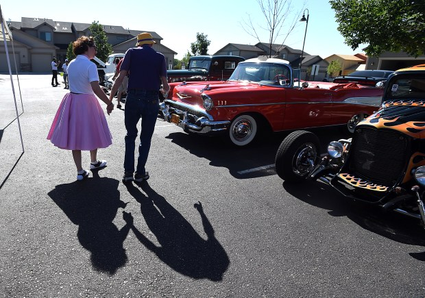 Art Kimble, right, walks with Jordan Bryson, Director of Health Care Services at Seven Lakes Memory Care in Loveland, toward his classic car on Thursday during a Happy Days car show at Seven Lakes Memory Care in Loveland. (Jenny Sparks/Loveland Reporter-Herald)