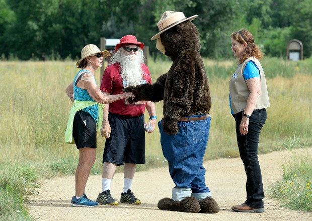 Julie Peters, left, and Santa Claus, also known as Jerry Julian, are thrilled to meet Smokey Bear while hiking Thursday at River's Edge Natural Area in Loveland. Smokey's helper, Environmental Education Coordinator for the city of Loveland, Michele Van Hare, far right, watches as they chat. Friday is Smokey Bear's 75th Birthday.(Jenny Sparks/Loveland Reporter-Herald)