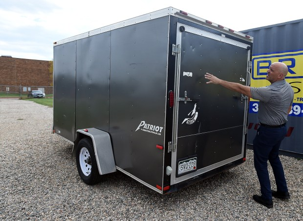 Berthoud High School Activities Director Michael DeWall shows where decals were removed from the school's marching band trailer on Monday, Sept. 16, 2019, outside Max Marr Stadium at the school in Berthoud. The trailer was stolen and was recently recoverd and returned. (Jenny Sparks/Loveland Reporter-Herald)