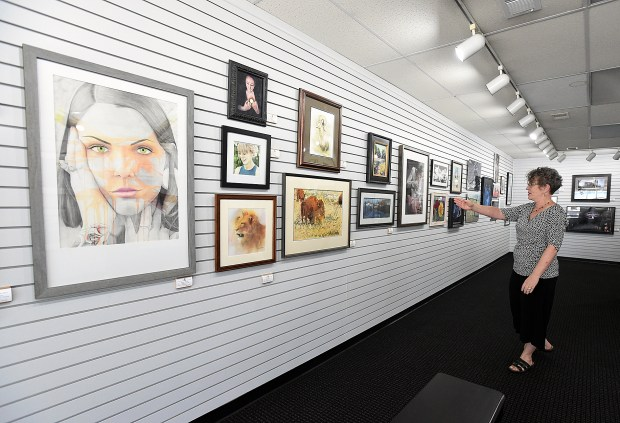 LOVELAND, CO - SEPTEMBER 9, 2019: Lincoln Gallery Director Jill Atchison shows off some of the pieces in the watercolor and pastel categories Monday, Sept. 9, 2019, in the gallery's Regional Fine Art Show in downtown Loveland. (Jenny Sparks/Loveland Reporter-Herald)