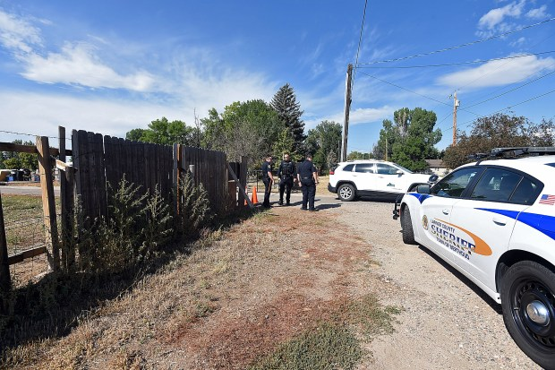 Larimer County Sheriff's deputies stand by as code enforcement employees leave a property at 860 Fourth St. SE on Wednesday after informing the owner that he was not complying with a court order that states people are not allowed to camp there. (Jenny Sparks/Loveland Reporter-Herald)