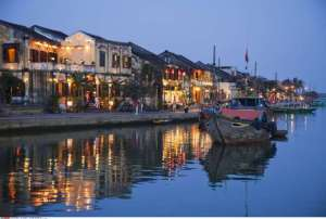 Buildings at the waterfront lit up at dusk, Hoai River, Hoi An, Vietnam
