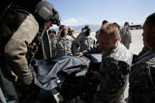 April 3, 2009- Bagram, Afghanistan: The body of Captain Petre Tiberius is unloaded from a helicopter by fellow Romanian soldiers and American medical personnel at Bagram Air Field in Afghanistan on April 3, 2009. The defense ministry in Bucharest, Romania announced Captain Petre Tiberius was killed in crossfire while leading a rapid intervention mission on Friday to support ISAF forces who had come under attack. Captain Tiberius was transported by helicopter to a forward surgical hospital but died in transit. Romania has lost 10 soldiers in Afghanistan.