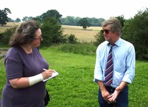 Harvey Sheldon being interviewed by Maev Kennedy of the Guardian; the fields in the background are part of the area threatened by renewed ploughing.
