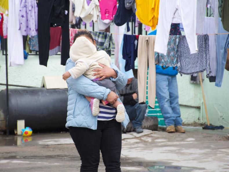 Alma, an asylum seeker from Guatemala, with her toddler daughter at an IRC-supported shelter in Mexico. She is holding her daughter while laundry dries near them.