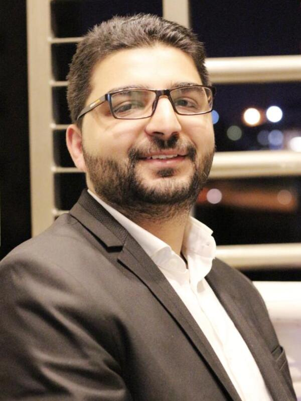 Dr. Abedalhaleem Albalasmeh, wearing a suit, smiles for the camera.