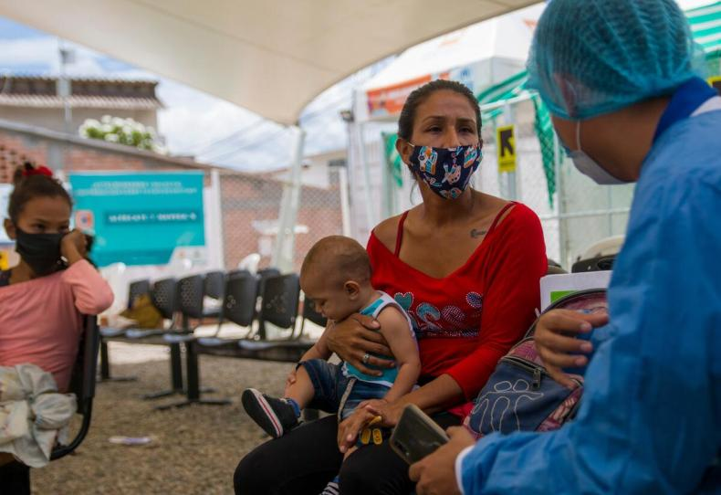 A health worker in protective equipment speaks with a woman who is sitting wearing a mask and holding her baby