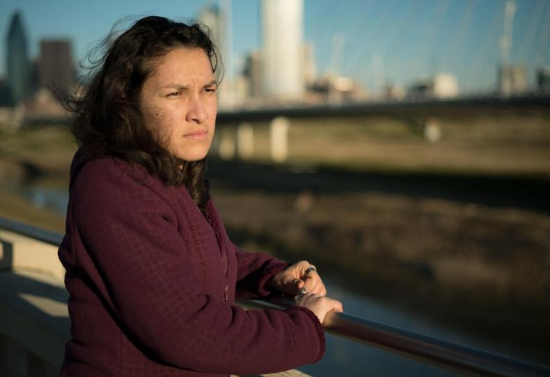 Valentina, a refugee from El Salvador, stands on a bridge in Dallas, TX, and looks out over the water.