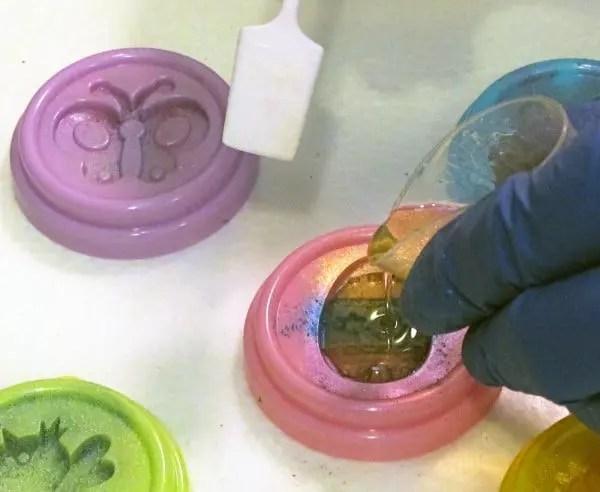 pouring polyurethane resin into a mold to make charms