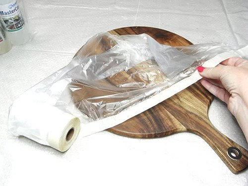 cover cheese board with plastic and secure with tape