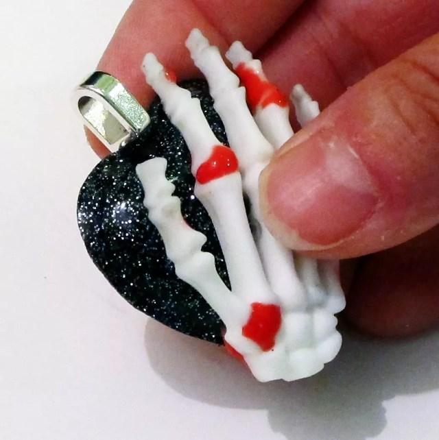 gluing a skeleton hand onto a resin heart