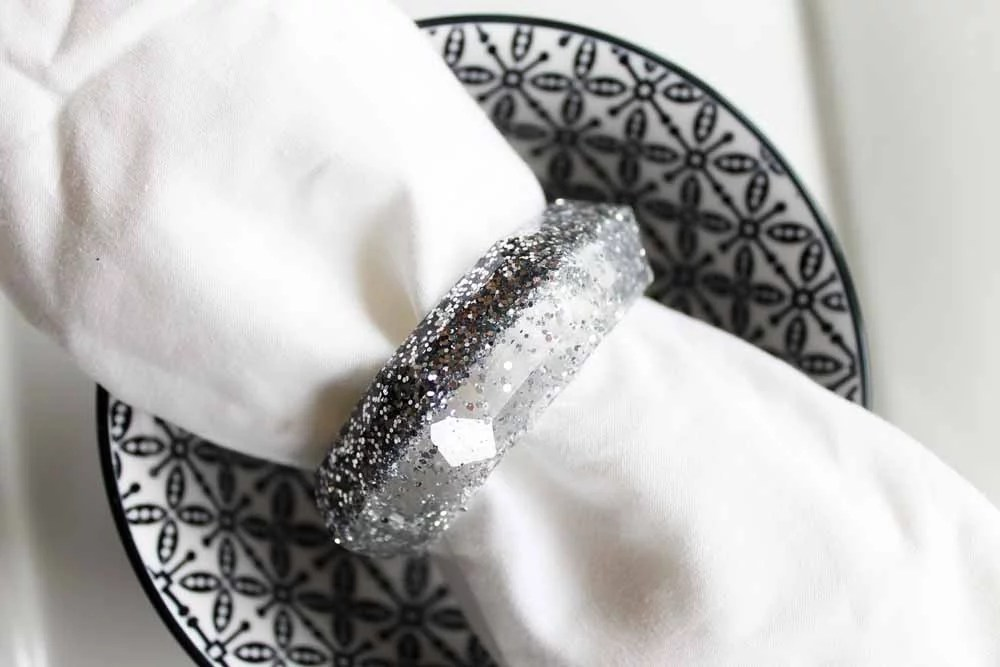 silver glitter resin napkin rings silver on black and white dish close up