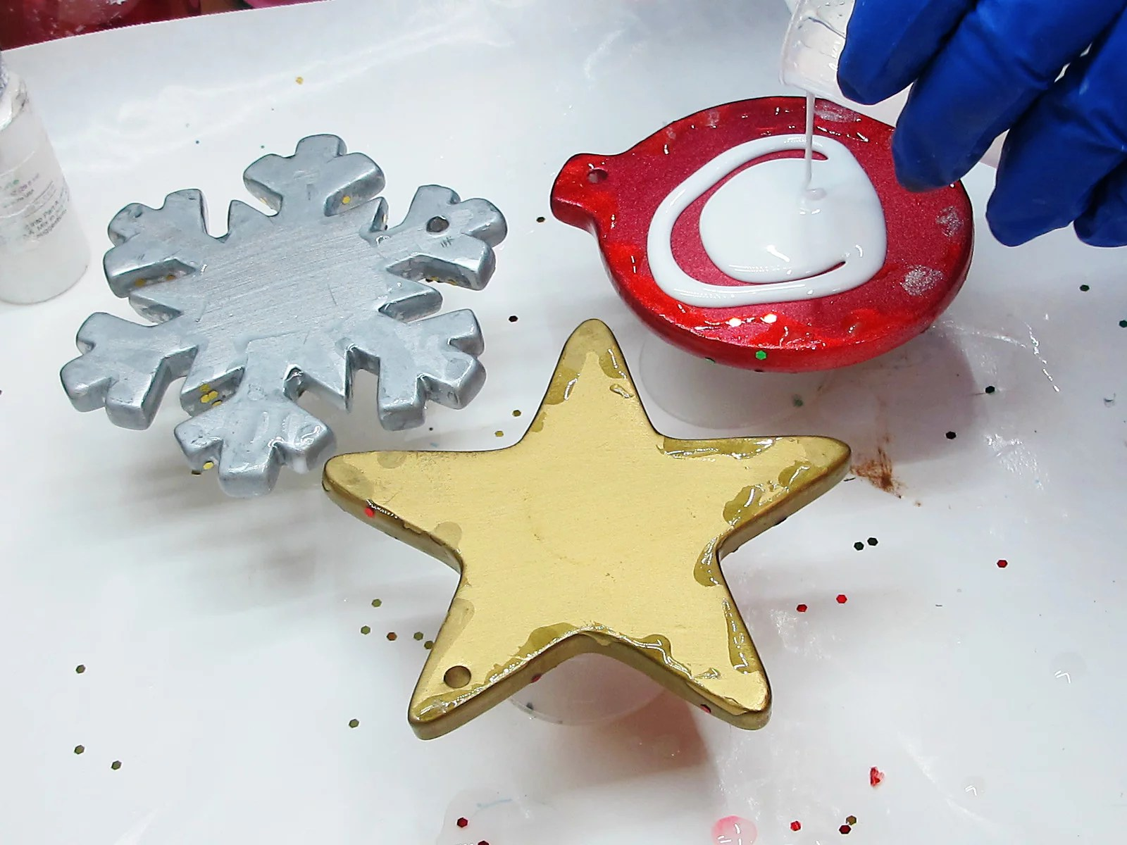 applying white resin to ceramic Christmas ornaments