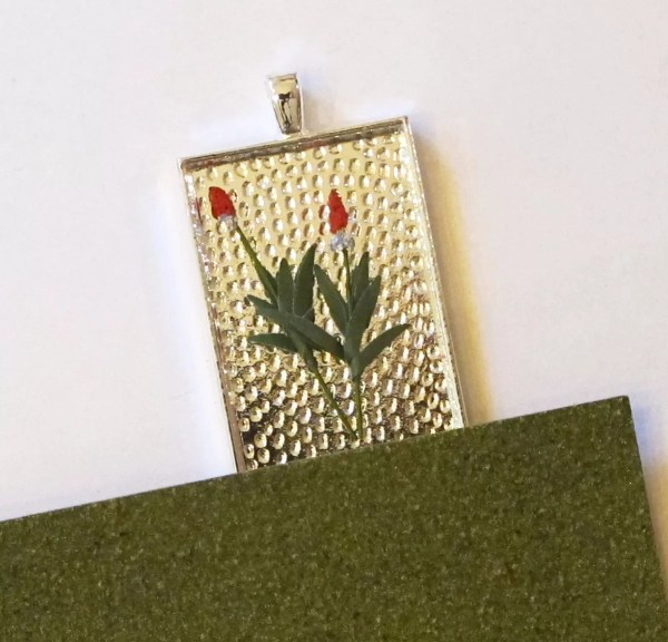 miniature flowers and grass in pendant