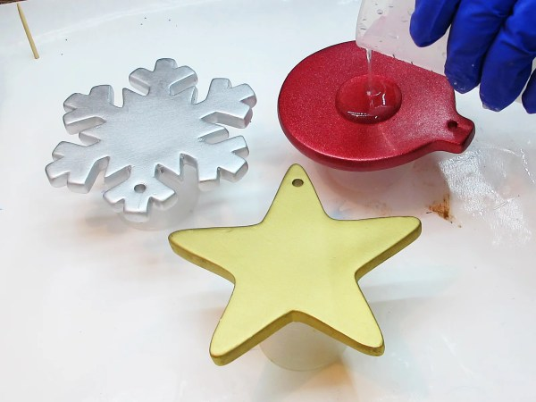 pouring clear resin onto Christmas ornaments